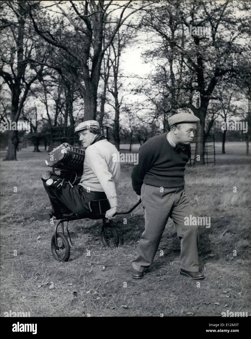 Feb. 24, 2012 - Losr's Penalty: It's always the big 'uns who tire first, and theh little Charlie drake ha to haul his bulky partner round the last hole like this. - Stock Image