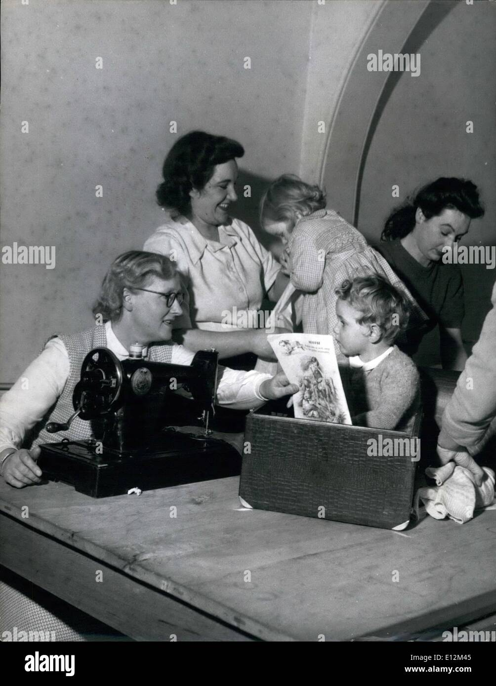 Feb. 24, 2012 - One way of keeping the children quite and occupied during the dressmaking class. This little boy sits inside the lid of a machine reading a comic. Mothers Take Their Babies To Dressmaking Classes: When the young mothers of Dover told Mr. G.H. Twaddle, head of Dover Technical College that they could not attend the afternoon dressmaking classes because they could get nobody to look after their children, her said, ''bringing the children with you'' - Stock Image