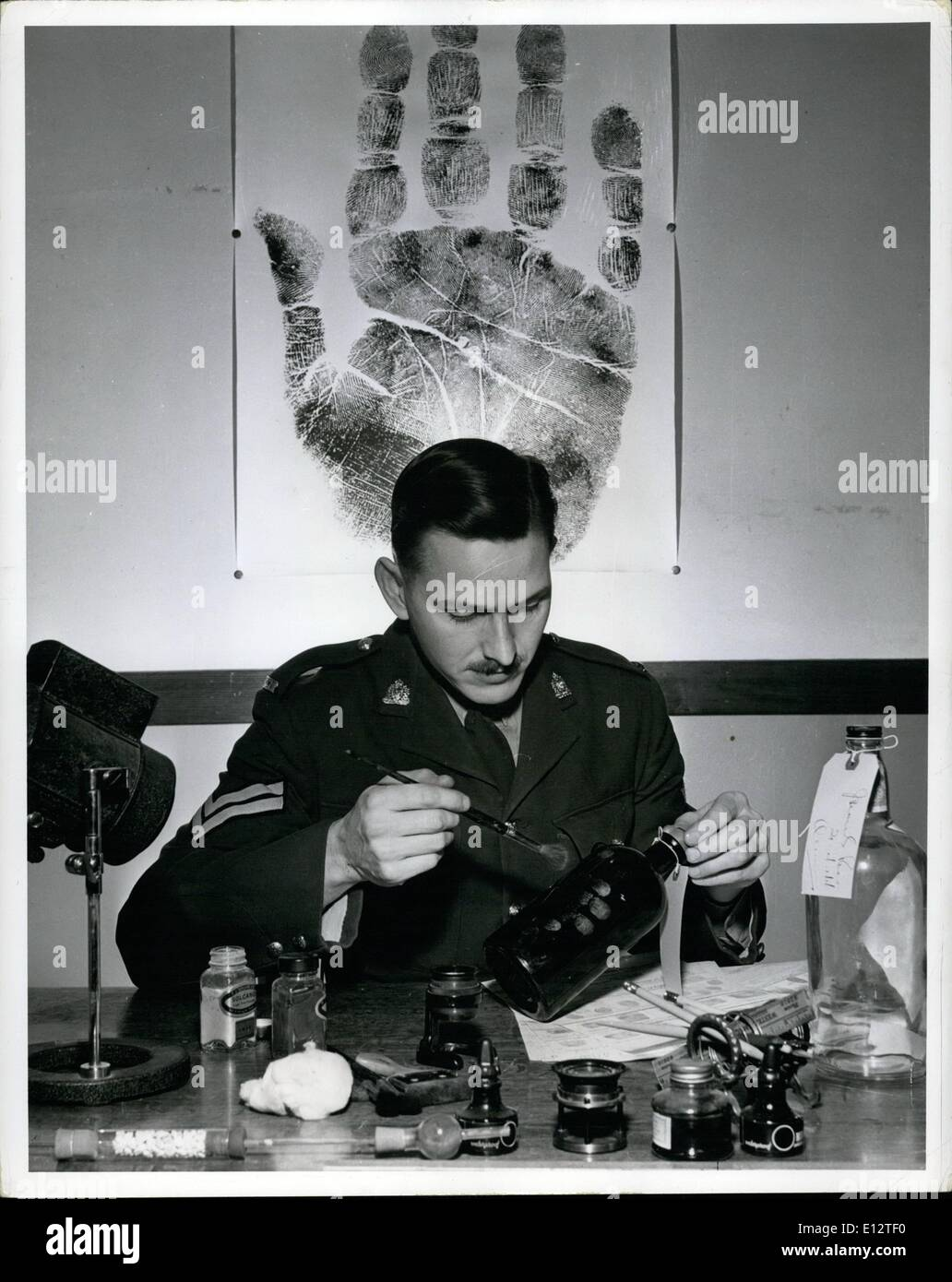 Feb. 25, 2012 - Corporal J.H.S.P. Jones, in charge of the R.C.M.P. Criminal Investigation Branch Photo and Fingerprint Section at Regina, Sask., examines a bottle for fingerprints. The bottle, evidence in a police investigation, was taken from the scene of the crime. - Stock Image
