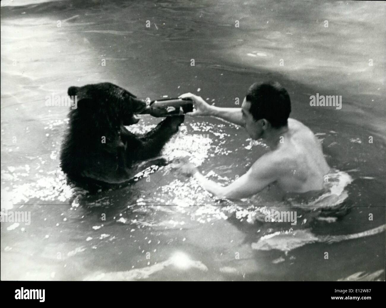 Feb. 25, 2012 - A Japanese bather shares his bottle of beer with another bather, this time a young bear. - Stock Image