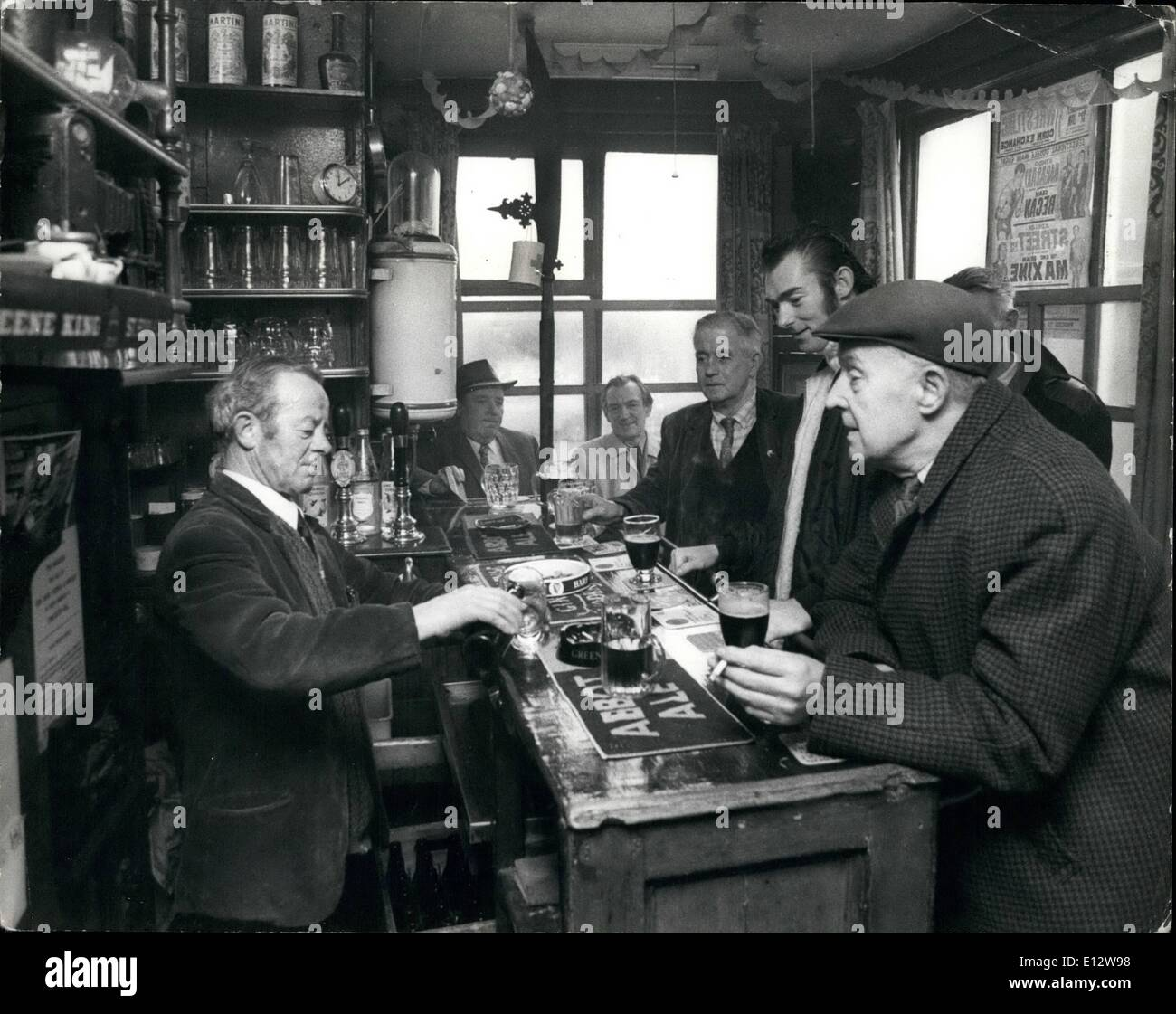 Feb. 25, 2012 - Ted McCallam serves customers in the pub and acknowledged as the smallest in the United Kingdom. It is The Nutshell at Bury St. Edmunds, Suffolk. - Stock Image