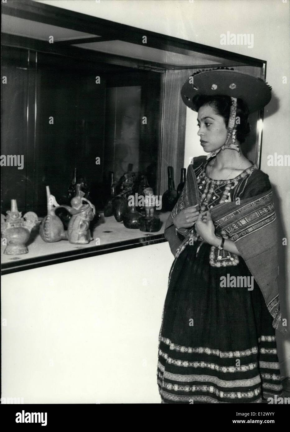 Feb. 25, 2012 - Peruvian Art Exhibition in Paris Today at Petit Palais, Paris opened a Peruvian Art Exhibition. OPS A young Peruvian Girl, in National Dress looks at very old statues in a window case. - Stock Image