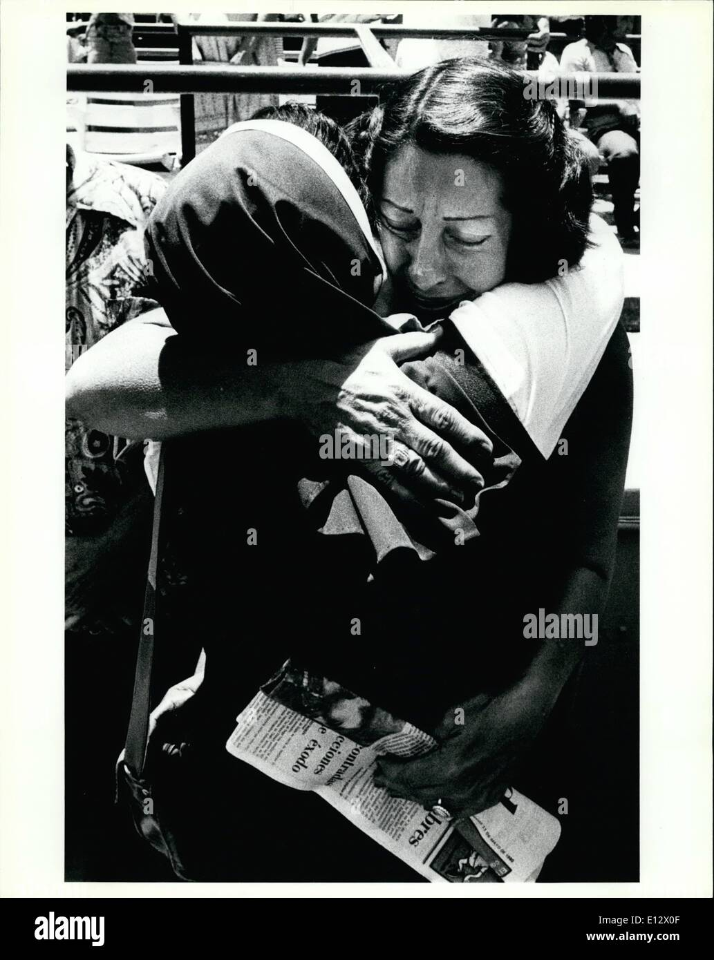 Feb. 25, 2012 - A Cuban refugee woman gives a tearful hug to a nun after the sister had helped deliver the first mass to the refugees since they arrived in the U.S. The mass was performed in the Orange Bowl in Miami. The Orange Bowl was used as a holding area for the refugees before they were move to processing centers in the Miami area. - Stock Image