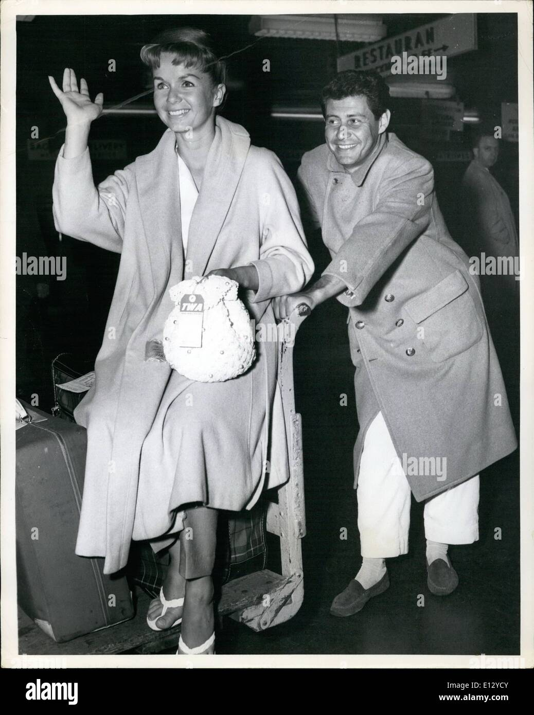 Feb. 26, 2012 - Idlewild Airport, N.Y., May 16. Pretty Debbie Reynolds gets an able assist from her singer husband Eddie Fisher with the baggage on their arrival from Los Angeles via TWA. They're here for a week-end business conference. - Stock Image