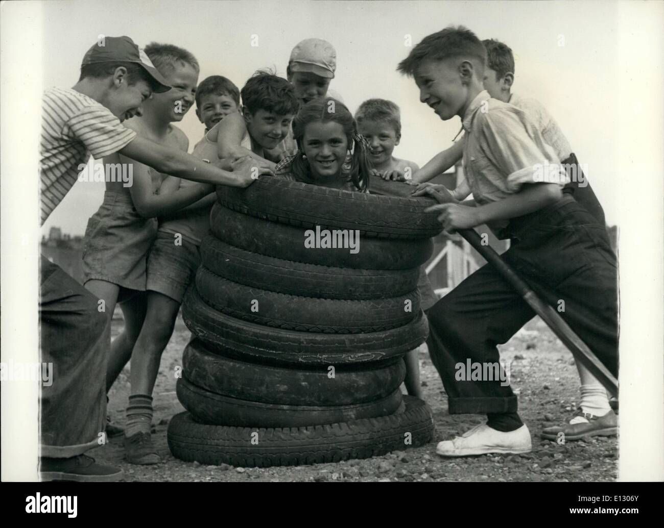 Feb. 26, 2012 - Old motor tyres are among the favorite toys and its surprising the number of games the kids invent with them. Here they use one of the girls, Anne Tatnell, as a Totem pole, and she seems to enjoy it. - Stock Image