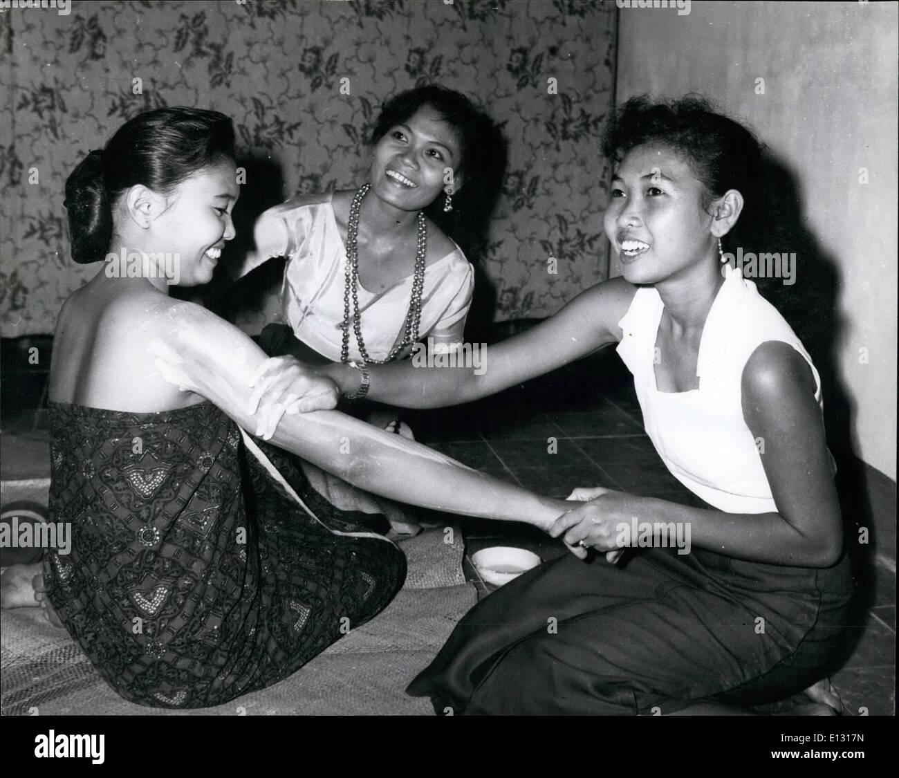 Feb. 26, 2012 - In a Royal dancing school in Indonesia : Pretty princess sri justia , 19, has ''lulur'' smeared on her arms by her co-princesses Sri Hatinah and Amirati. ''Luxlur'' is a native make - up liquid like calomine which makes the skin look whiter. A fair skin is essential to beauty in the East. - Stock Image