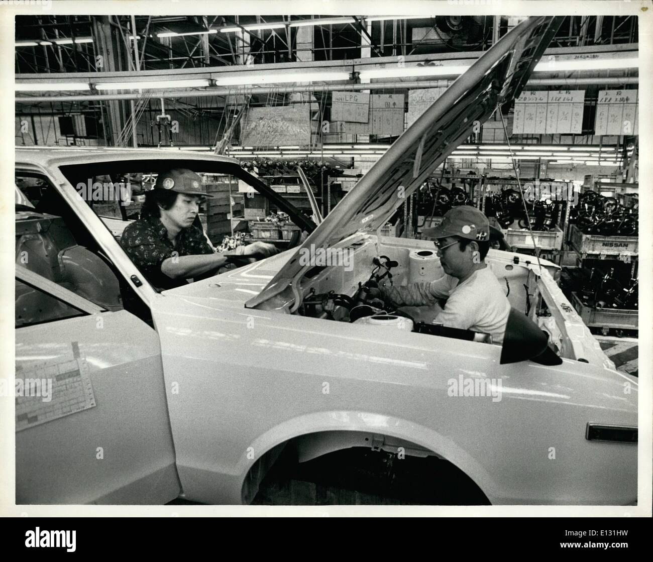 Feb. 26, 2012 - Tuesday, April 10th, 1979. Nissan Motors Oppama Plant, Oppama, Japan. Nissan Motor Co. Ltd. produces three models of Datsun automobiles at their Oppama Plant. The Nissan President, Datsun Bluebird and Datsun 510. OPS: Assemby line workers on the trim line where windshields, front grills, headlights (manufactured by General Electric in the United States) are added to the cars. - Stock Image