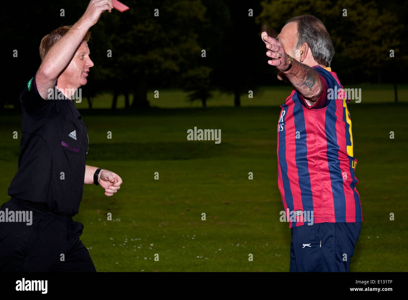 Referee holding up a red card sending off a football player during a fun event inside Camperdown Country Park in Dundee, UK - Stock Image