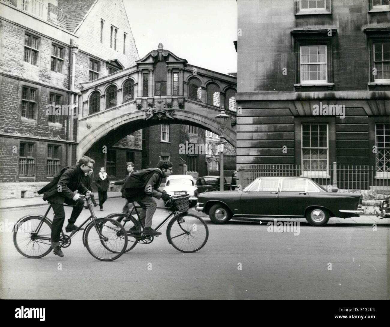 Feb. 26, 2012 - Bike and the Bridge of Signs... Bicycles are the rule in Oxford - and Colin Day (right) and Charles Garner use them to get to lectures and tutorials out of college - but after years of use the turn into mouldering, forgotten wrecks... Before... and see 25 for after. - Stock Image