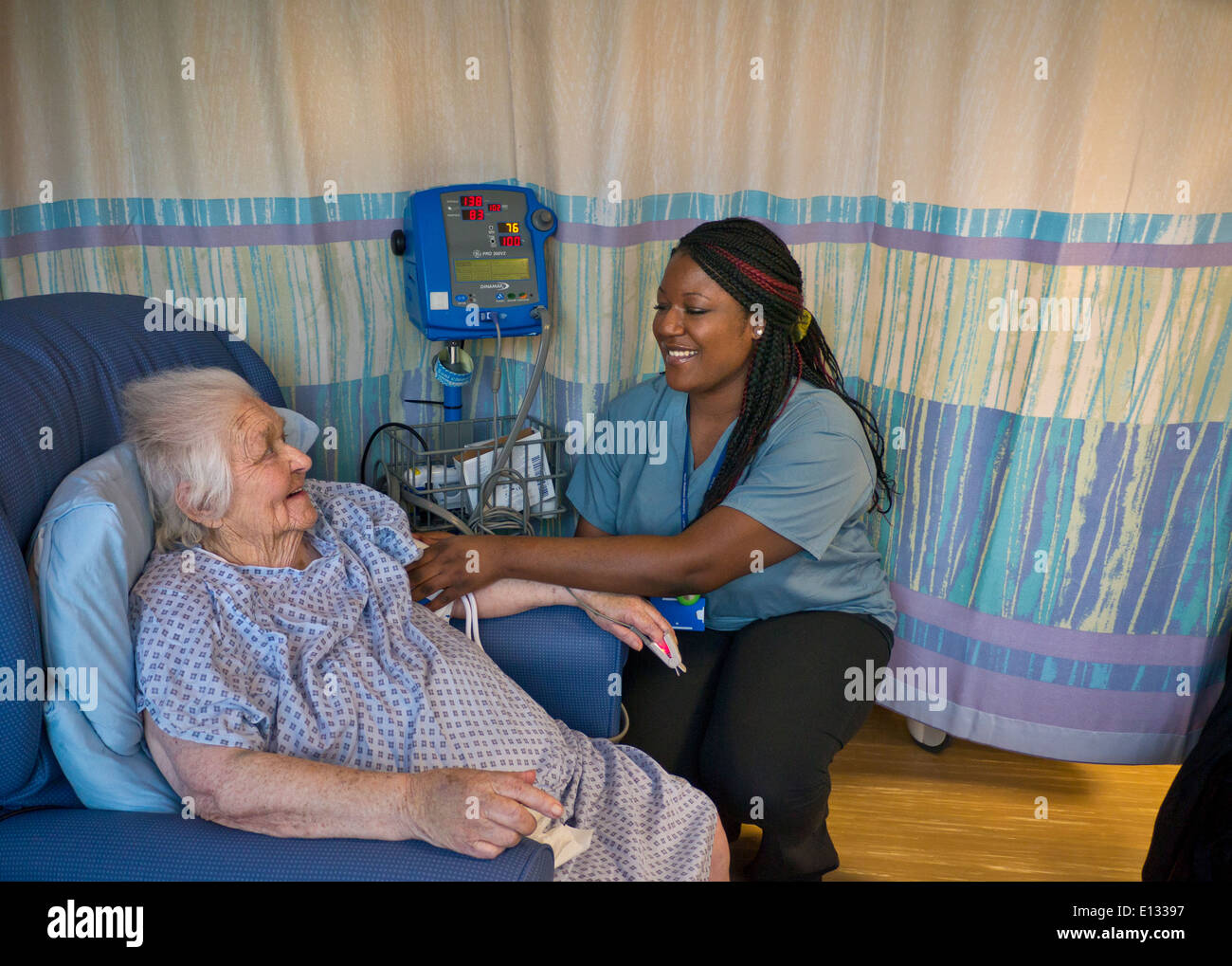 Contented elderly lady in hospital ward having her blood pressure taken by attractive smiling hospital nurse - Stock Image