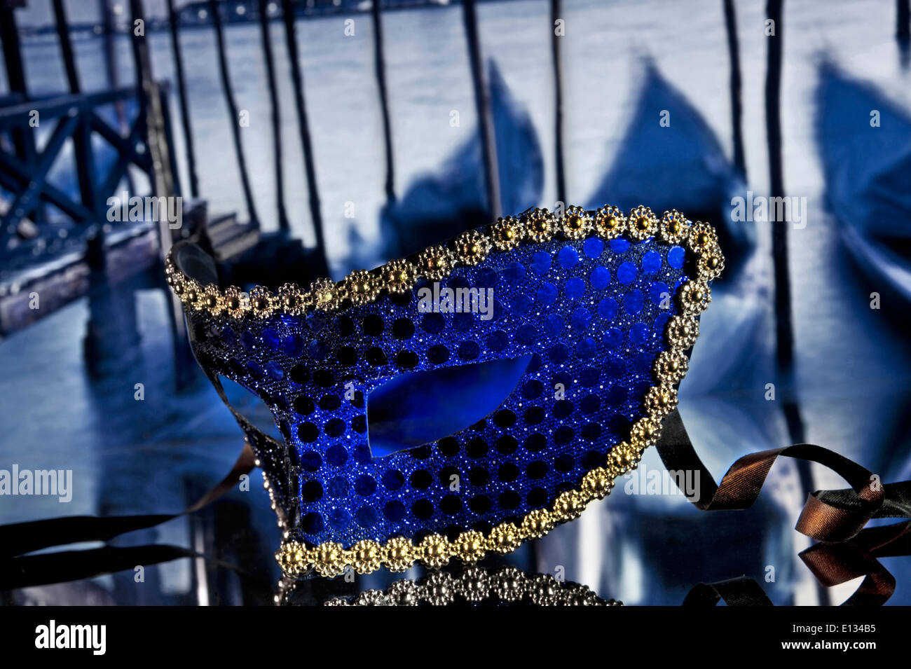 Atmospheric traditional Venetian carnival mask on cafe table with gondolas behind St Marks Square Venice Italy - Stock Image