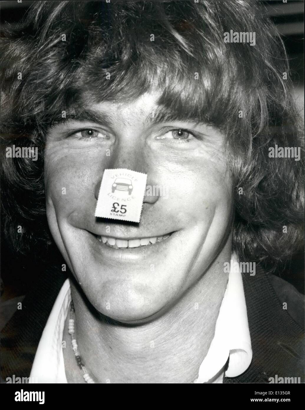 Feb. 28, 2012 - August 11th 1980 Vehicle license stamps to help the motorist. Vehicle licence stamps go on sale today at all post offices so as to help motorists to save for their licenses during the year. The £5 stamp may be used to buy any type of motor vehicle license. Photo Shows: James Hunt the former champion motor racing driver can find only one place to stick the special stamp, and that is on his nose. - Stock Image
