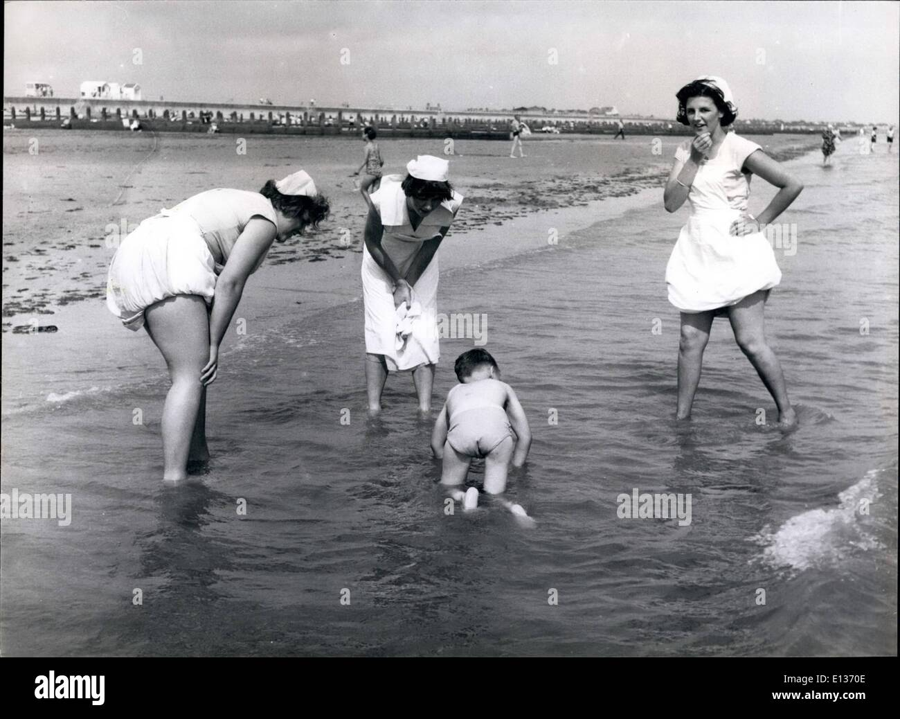 Feb. 28, 2012 - The schoolgirl ''nurses'' encourage one of their charges to paddle on all fours during a trip to the beach from - Stock Image