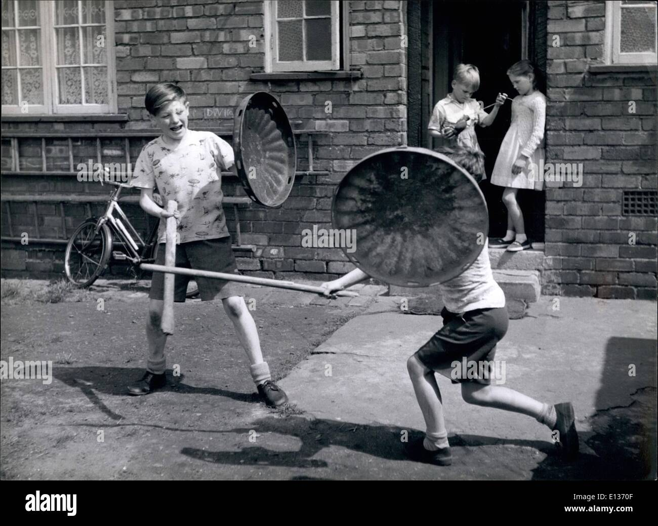 Feb. 28, 2012 - Dustbin lids become shields and sticks become sword as John plays soldiers with his friend Trevor. - Stock Image