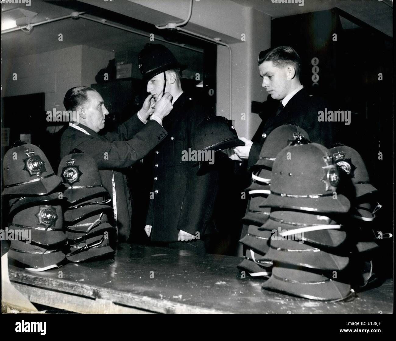 Feb. 29, 2012 - Police recruits at the hat shop: Helmets of all shapes and sizes are kept both at the Metropolitan Police Training School, Hendon and at the Divisions to which the constables are posted after posing out. Constables Bottrill and Birthchnell are getting their's now. - Stock Image