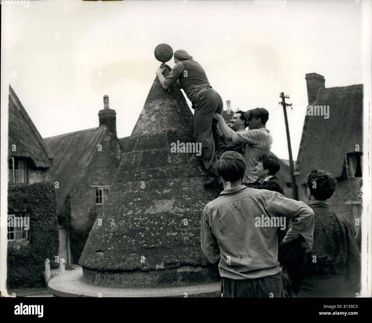 Feb. 29, 2012 - Climbing the Bulter Cross , which has stood on the village green for 300 years, is Ernest Driver, - Stock Image