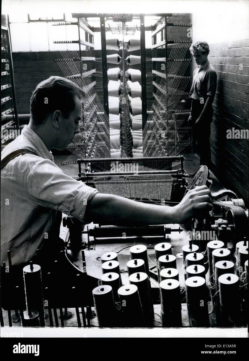 Feb. 29, 2012 - 11. For Bobbin Net; Winding Thread off the cones on to the bobbins which will be used later in making bobbin net. The bobbin are threaded on square Sedition Spindles. - Stock Image