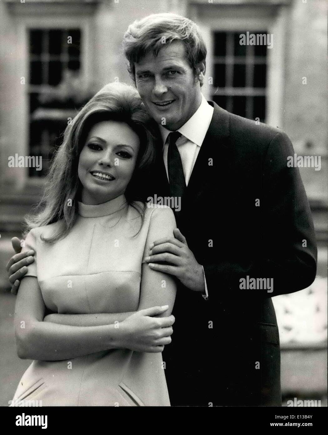 Feb. 29, 2012 - Stars at Woburn Abbey. Film stars Roger Moore and Claudie Lange, will be spending much of their time this week at Woburn Abbey, Bedfordshire by courtesy of the Duke and Duchess of Bedford, though not so much for pleasure as to work! For together with five of six hundred extras, Roger and Claudie are shooting their latest film, 'Crossplot', which also stars Martha Hyer and Alexis Kenner in the beautiful grounds of the abbey. Roger Moore and Claudie Lange pose for a picture during a break from filming 'Crossplot' in the grounds of Woburn Abbey. - Stock Image