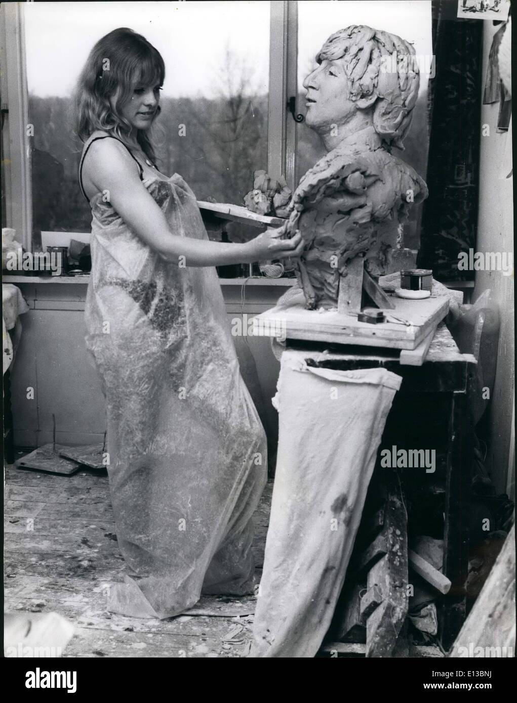 Feb. 29, 2012 - Working in clay is dusty work- hence the wrapping round sculptress Liz Moore while she works on a bust of Beatle John in her Surrey studio. - Stock Image