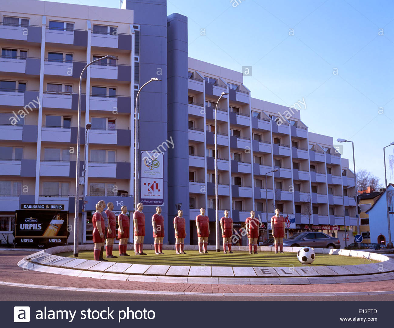 Eleven Freunde football players - all white, in red strip, as statues in the middle of a roundabout in Kaiserslautern, Germany. - Stock Image