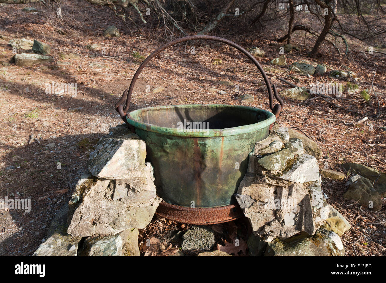 Old copper cauldron resting on a fire pit. - Stock Image
