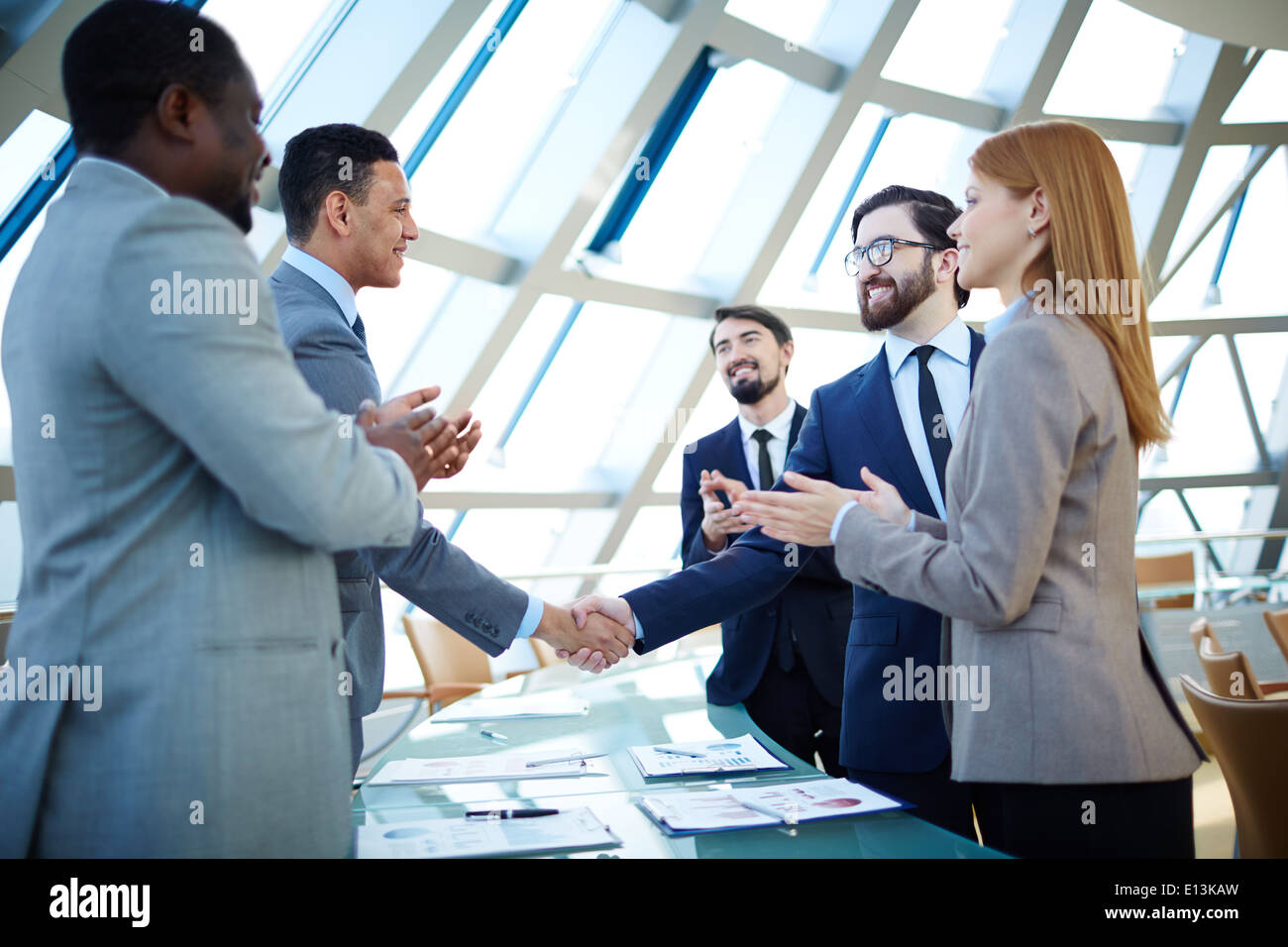 Group of business people congratulating their colleagues with striking grand deal - Stock Image
