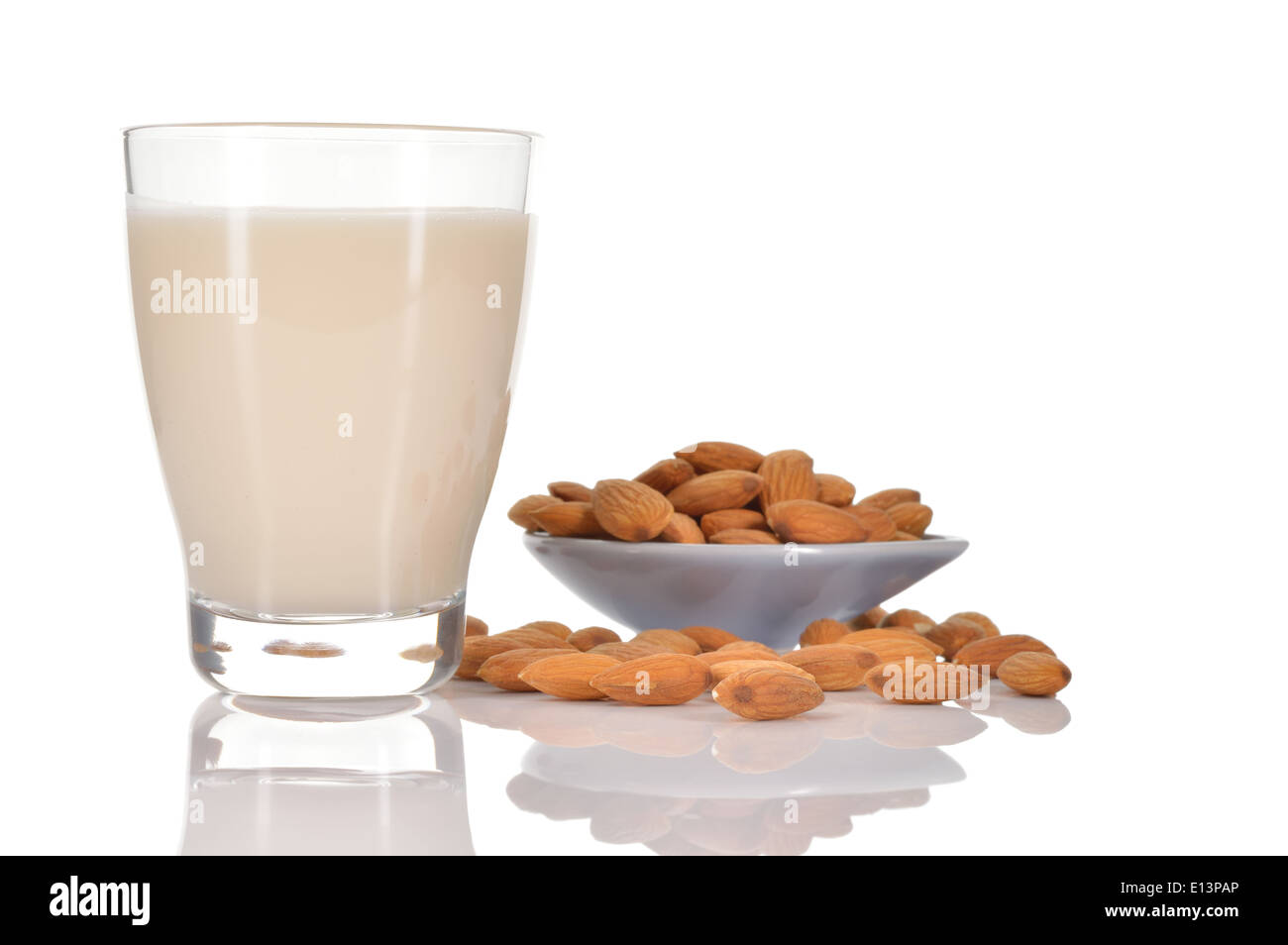 Almond milk as a substitute for dairy milk. Glass of almond milk and few almonds on a saucer isolated on white background. - Stock Image