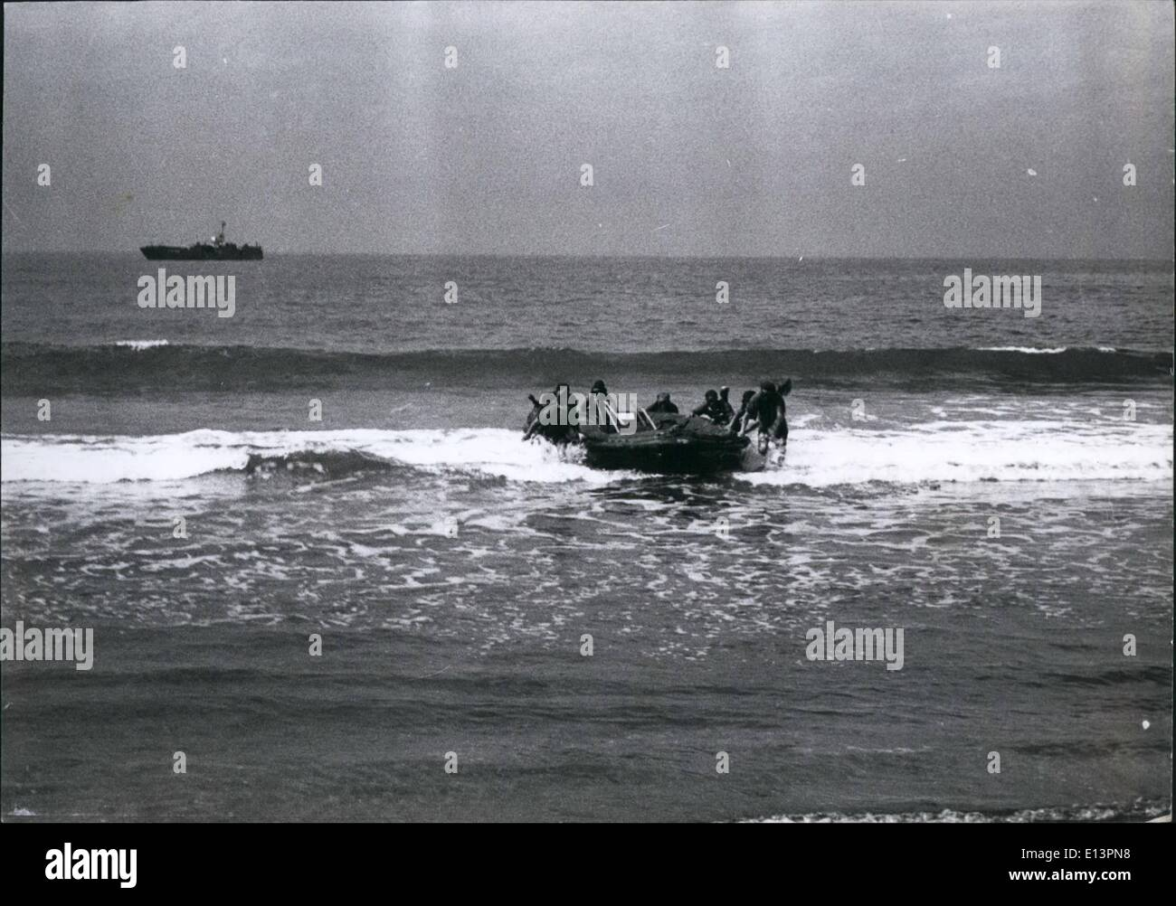 Mar. 22, 2012 - The frogmens assult is usually carried out on a dark moonless night, but for training purposes they carry out exercises in daylight. The frogmen are seen pulling their rubber raft ashore containing thier demolision explosives and arms. In the distance is the landing craft which has brought them near beach. - Stock Image