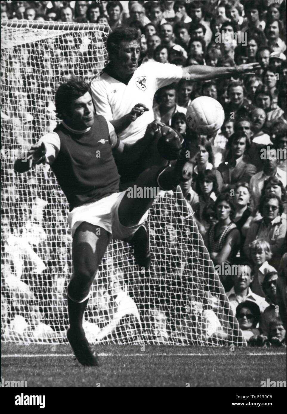 Mar. 27, 2012 - Toling It.: Malcolm MacDonald (Arsenal) reaches the ball with his toe 5 feet above the ground. In close attendance is Bristol City's Geoff Merrick. - Stock Image