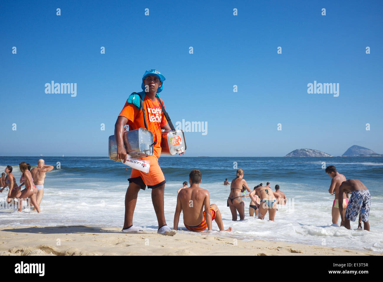 RIO DE JANEIRO, BRAZIL - JANUARY 24, 2014: Brazilian beach vendor selling snacks and Mate Leao, a brand of iced - Stock Image