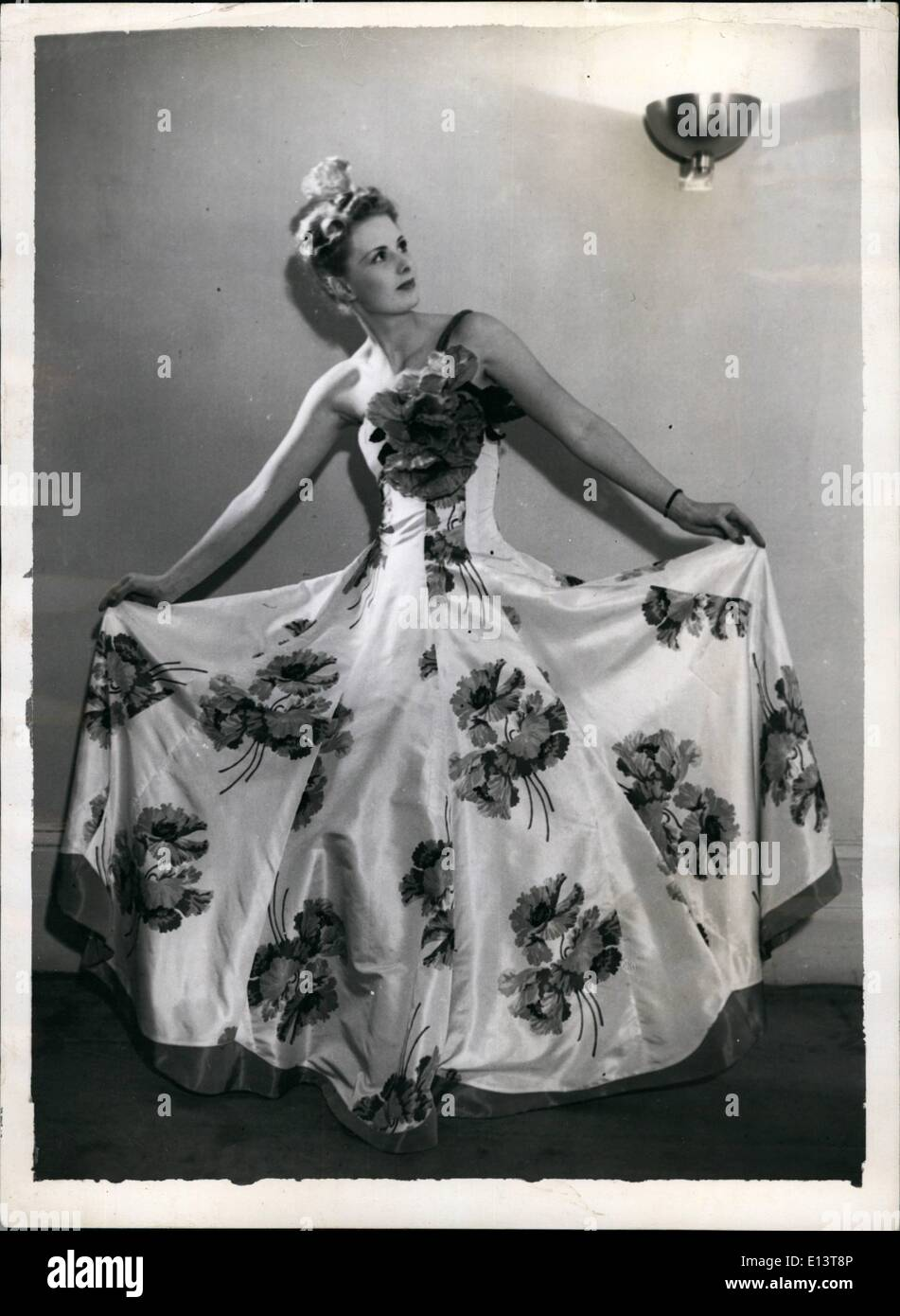 Mar. 27, 2012 - New Creations for the evening . A smart creation for evening wear by tinling. It is in white Taffeta and Features a bold design of Large red poppies. The bodice is strapless and is decorated with a large bunch of poppies. - Stock Image