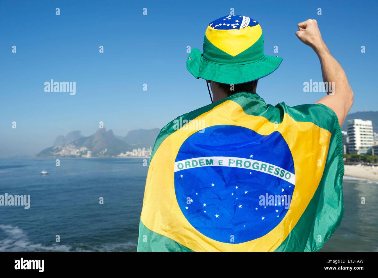 Brazilian football soccer player wearing flag and hat in front of Ipanema  Beach city skyline Rio de Janeiro Brazil 87aa78913d8
