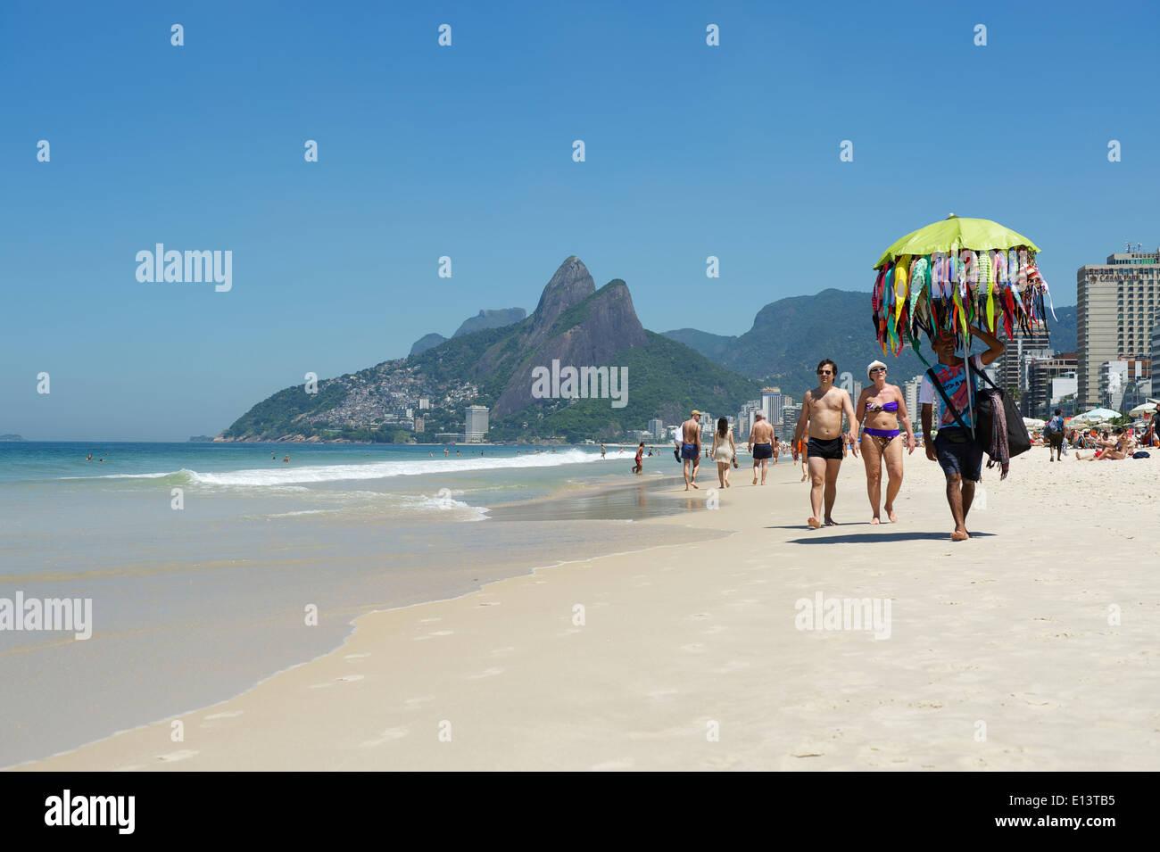 RIO DE JANEIRO, BRAZIL - MARCH, 2013: Beach vendor selling bikinis walks past morning beachgoers Ipanema Beach Rio de Jane - Stock Image