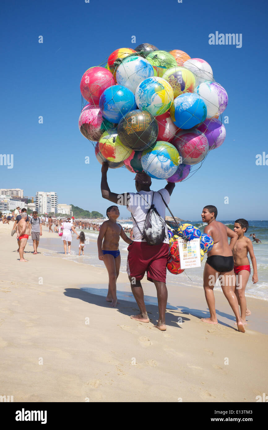 RIO DE JANEIRO, BRAZIL - JANUARY 20, 2014: Beach vendor selling colorful beach balls carries his merchandise along Ipanema Beach - Stock Image