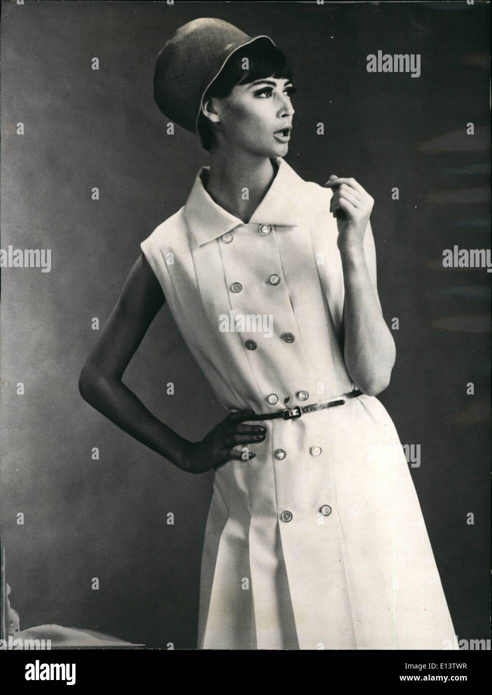 Mar. 27, 2012 - Long after the Spring collections, dress designers are still presenting their latest creations. OPS: A lovely model presents a sleeveless dress by Jacques HEIM in while linen, with double buttoning. - Stock Image