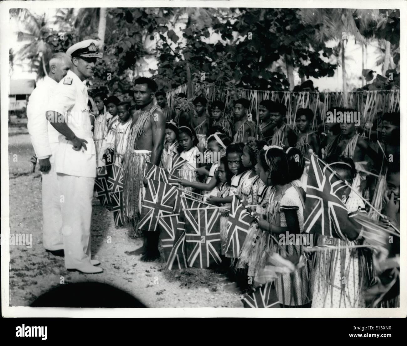 Mar. 27, 2012 - Duke of Edinburgh at Christmas Island: The Duke of Edinburgh with Mr. Percy Roberts the District Commissioner (left) talking with some of the Gilbertese schoolchildren on Christmas Island. During his visit to their village, the Duke watched demonstrations of thatching climbing and coconut husking. He was entertained by traditional songs and dances performed by the villagers. - Stock Image