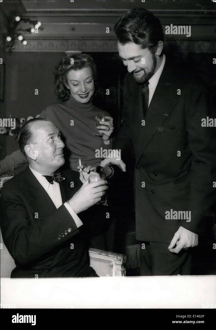 Mar. 31, 2012 - Noel Coward the famous English author and playwright (seated), has some champagne which the French actor Jean Claude Pascal is smilingly pouring into his glass. The young stage actress Gisele Preville seen in the centre. Picture taken at Sarah Bernhardt Theatre where Noel Coward attended Edwidge Feulillere's farewell performance in Duma's famous play ''La Dame Aux Camelias''. Jean Claude Pascal plays the role of Armand Duval and has grown a beard for the occasion. - Stock Image