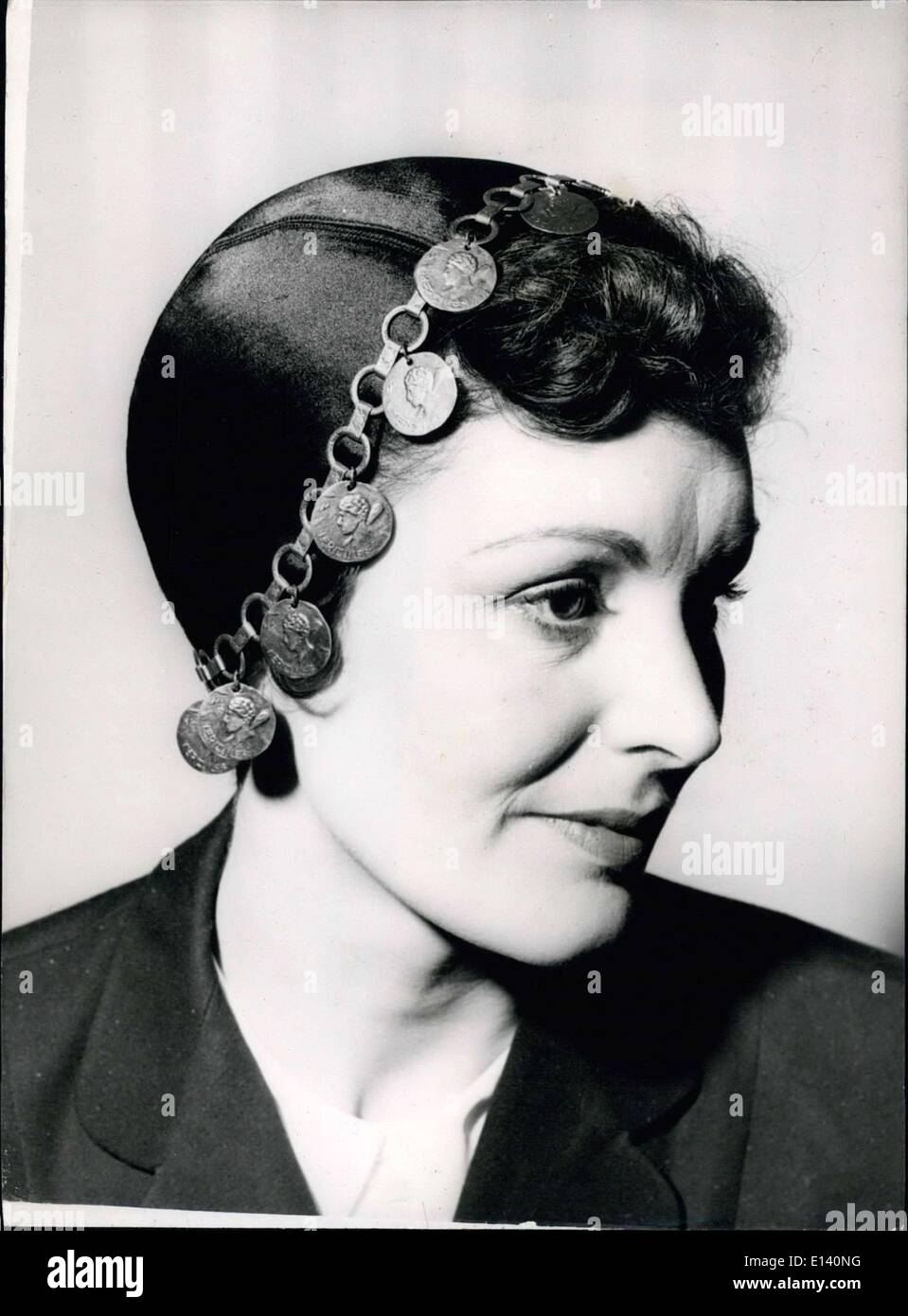 Mar. 31, 2012 - The latest in hat fashion : Juliet cap trimmed with gold coins : photo shows The black satin Juliet cap, trammed with gold coin round the edge - seen in the Simone Mirman collection of new millinery. - Stock Image