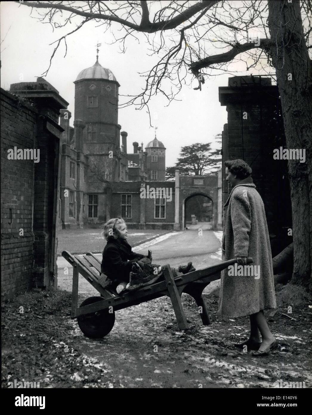 Mar. 31, 2012 - A countess collects wood for the fires of the ancestral home: Lady Darnley wheels a barrow of legs to Cobham hall, when wood is used as an economy messure whenever possible. Her daughter Harriot has a ride. - Stock Image