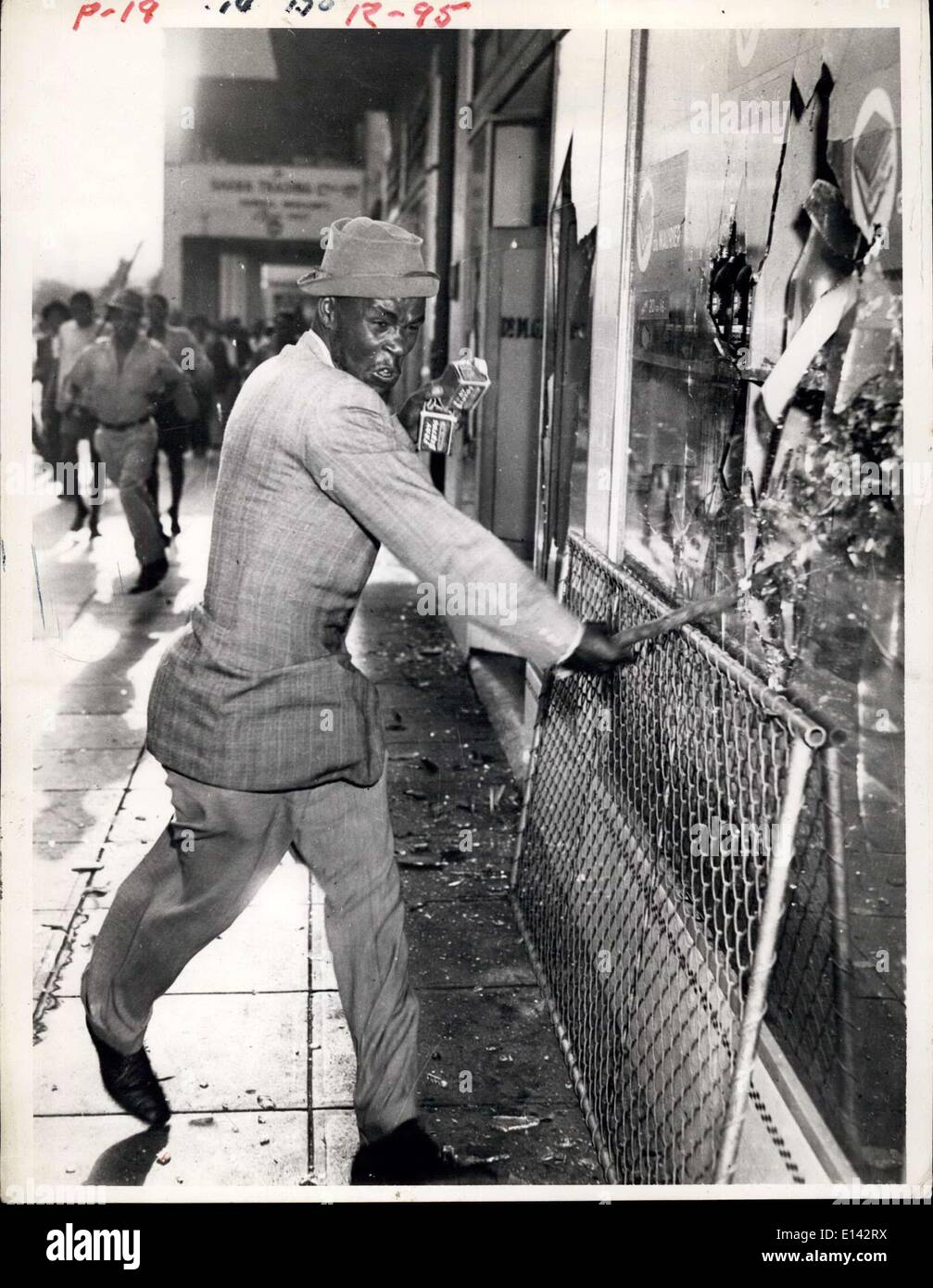 Apr. 04, 2012 - Durban Riots. Hate and brutal desire to destroy are expressed in the face and action of this well-dressed native who was caught by a cameraman as he smashed the plate glass window of an Indian shop on Friday. In his hand are two tins of meat looted from another wrecked grocery store. - Stock Image