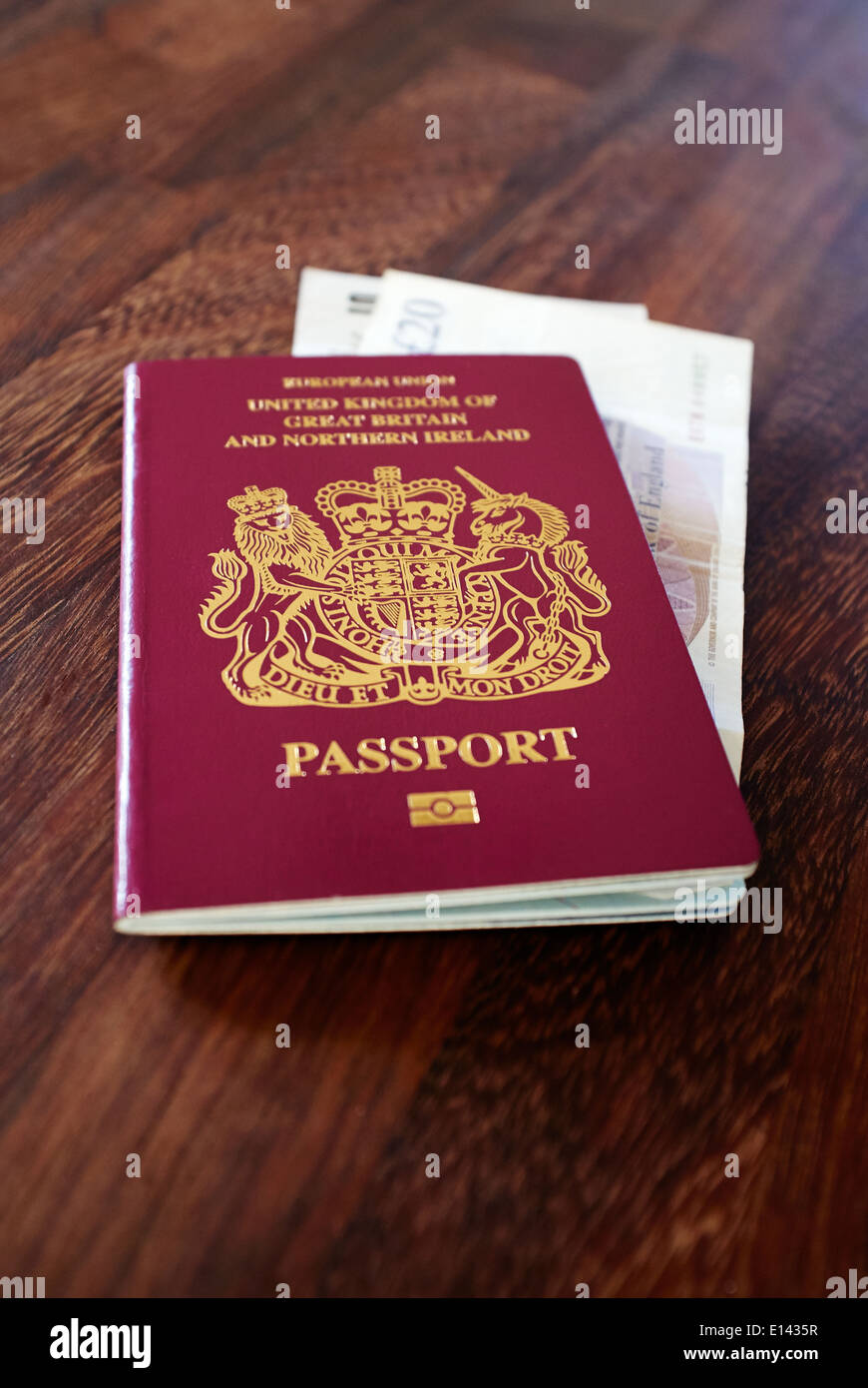 UK Passport with GBP Sterling bank notes on a dark wood table top. - Stock Image