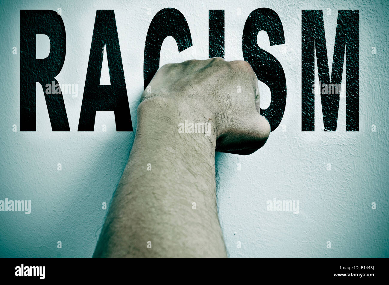 a man punching the word racism, depicting the concept of the fight against racism - Stock Image