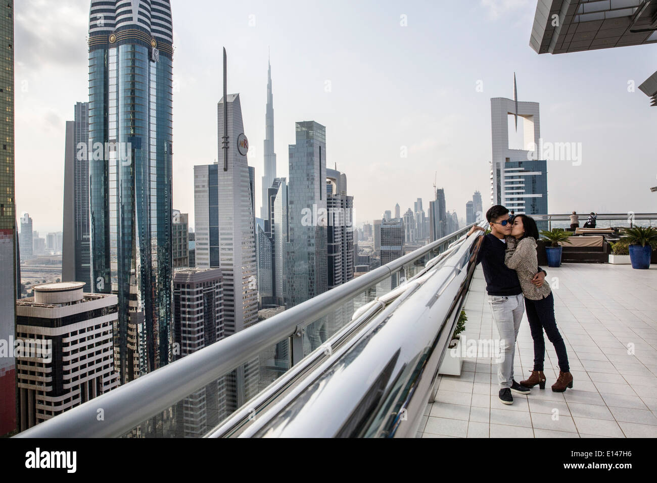 United Arab Emirates, Dubai, financial city center with Burj Khalifa, Asian couple kissing un rooftop of Sheraton Hotel - Stock Image