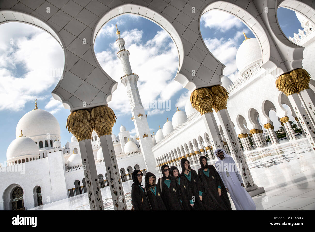 United Arab Emirates,  Abu Dhabi, Sheikh Zayed Grand Mosque. Group of tourists, dressed conform the dress code, taking picture - Stock Image