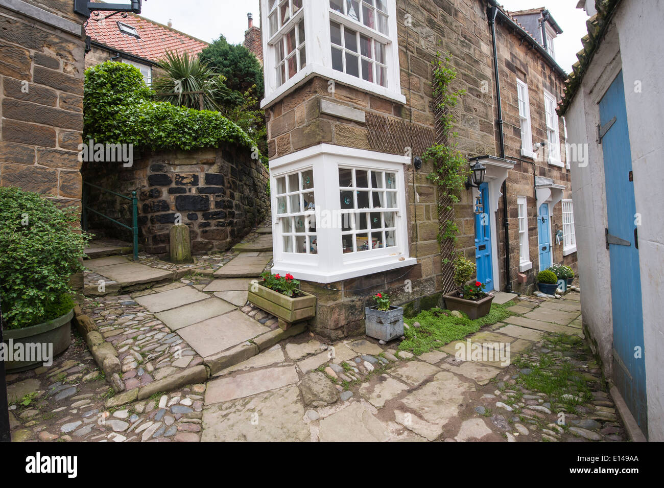 Corner of old country cottage building in english rural village with cobbled footpath on hill Stock Photo