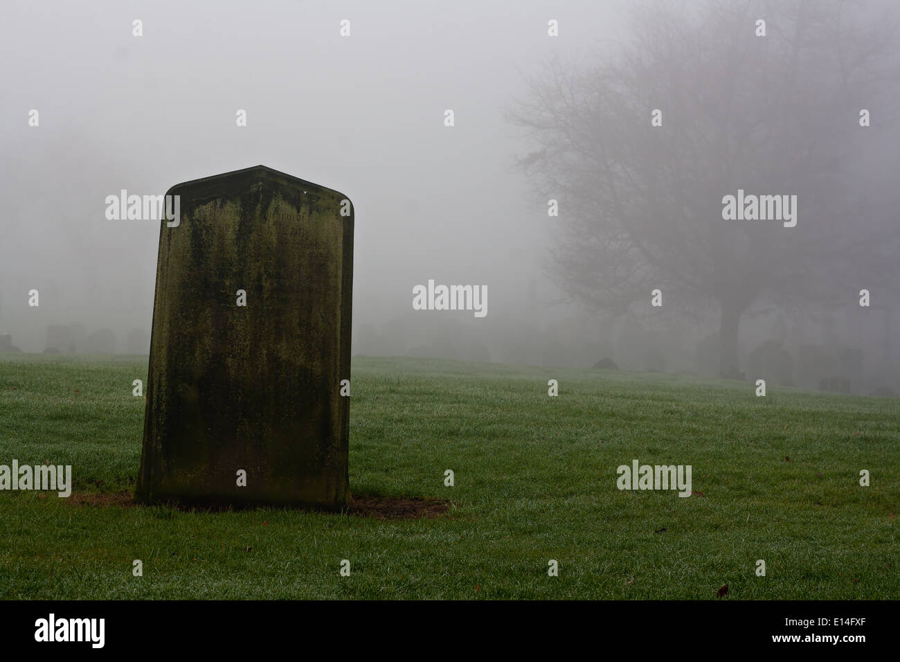 Spooky old graveyard on a foggy winters day - Stock Image
