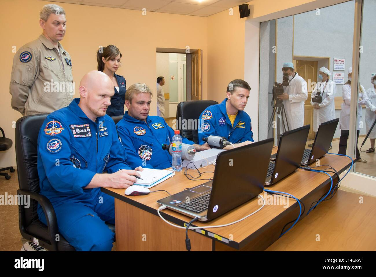 ISS Expedition 41 crew members Alexander Gerst of the European Space Agency (left), Max Suraev of the Russian Federal Space Agency, center, and Reid Wiseman of NASA practice rendezvous techniques on laptop simulators at the Cosmonaut Hotel May 21, 2014 in Baikonur, Kazakhstan. The trio will launch on May 29 in the Soyuz TMA-13M spacecraft from Baikonur for a 5 ½ month mission on the International Space Station. - Stock Image