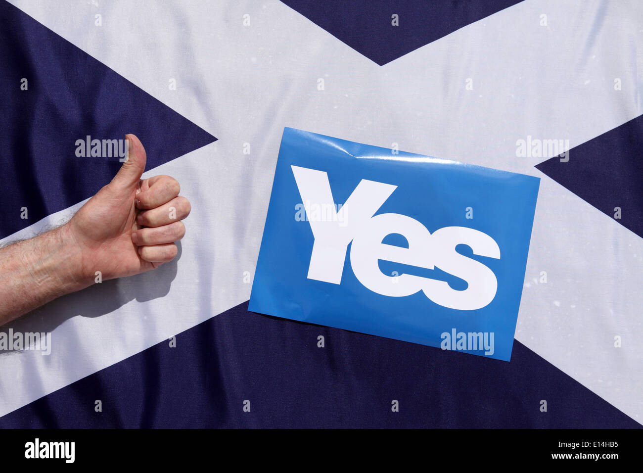 A thumbs up sign in front of a Scottish Saltire flag and a yes sign. - Stock Image