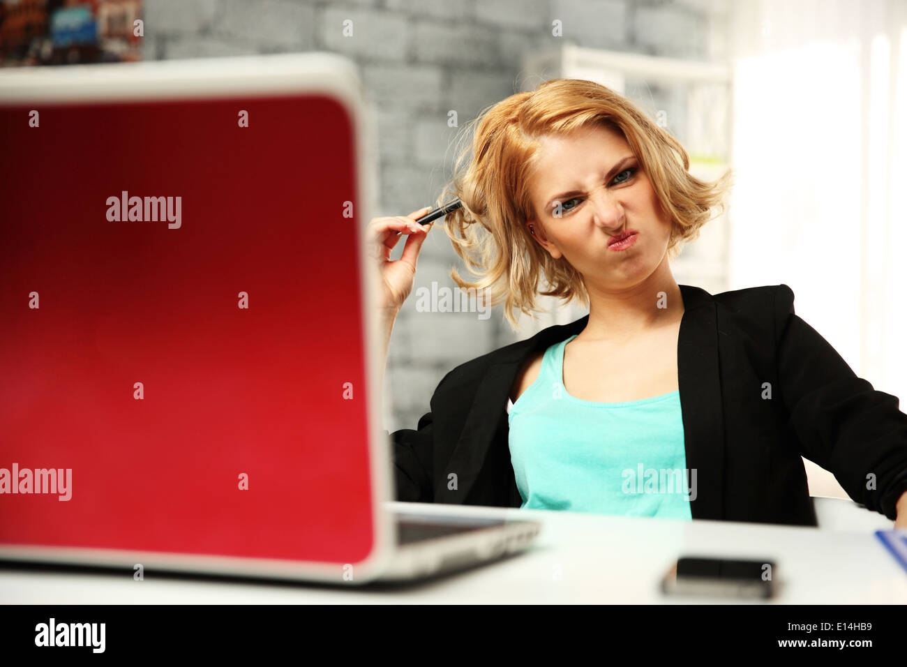 Young funny woman sitting at her workplace in office - Stock Image