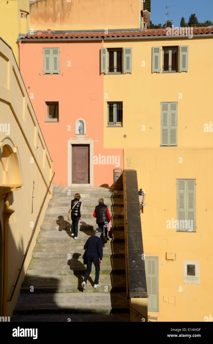 Tourists Climbing Steps to the Old Town and Bright Yellow & Orange Town Houses  Menton Alpes-Marittimes France - Stock Image